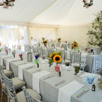 Rows of long tables with grey table cloths, set for the wedding breakfast in a marquee decorated with opulent floral displays and views of the garden