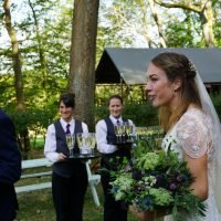 The groom and his bride, carrying her bouquet, walk through their woodland wedding setting, watched by serving staff holding trays of champagne