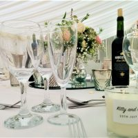 Wedding table dressed in white table cloth, with champagne flutes, cutlery, candles and a beautiful, central floral display